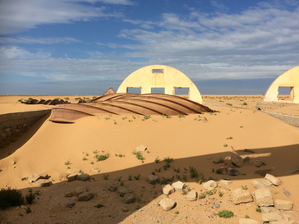 An old military base getting swallowed up by sand.